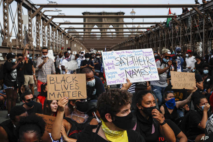 Protesters take a knee before continuing their march on the Brooklyn Bridge after attending a memorial service for George Floyd…