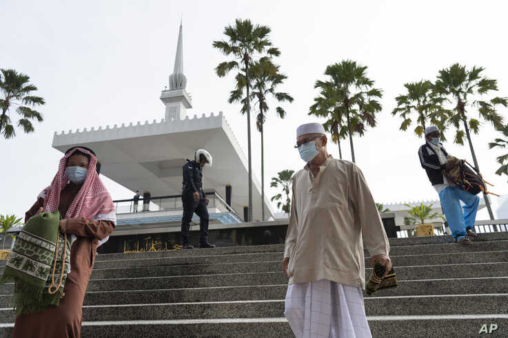 A police officer arrives to disperse Muslims praying outside the closed National Mosque to celebrate Eid al-Fitr, the Muslim…