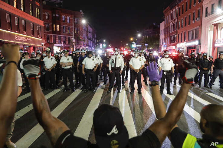 Protesters take a knee on Flatbush Avenue in front of New York City police officers during a solidarity rally for George Floyd,…