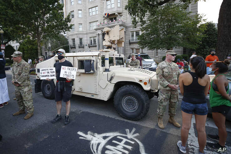 Demonstrators talk to National Guard soldiers as they protest Saturday, June 6, 2020, near the White House in Washington, over…
