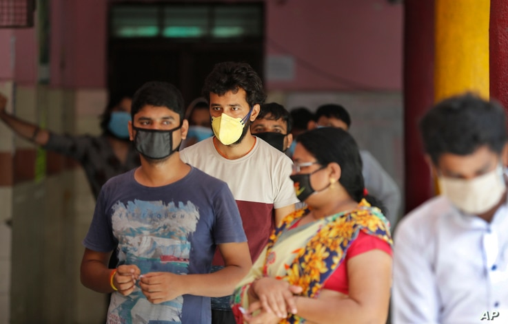 People wait in a queue for the COVID-19 rapid antigen test in New Delhi, India, Wednesday, June 24, 2020. India records the…