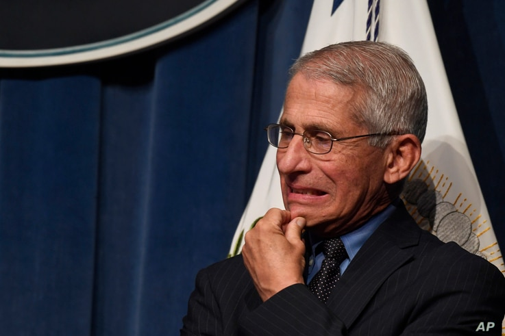 Dr. Anthony Fauci, right, director of the National Institute of Allergy and Infectious Diseases, listens during a news…