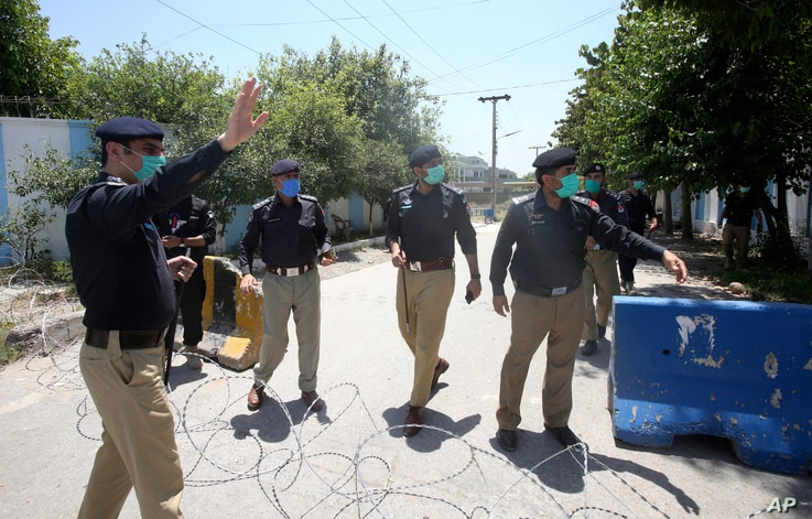 Pakistani police officers stand guard at a checkpoint of a restricted area to help contain the spread of new coronavirus, in…