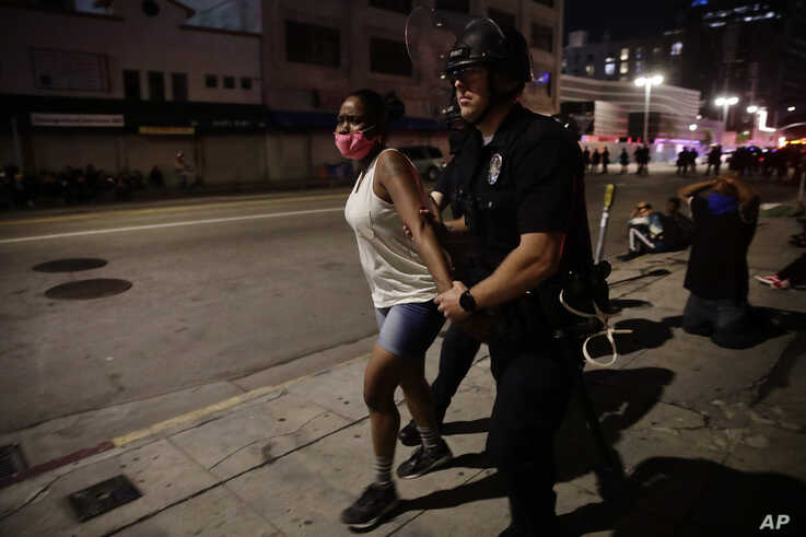 A police officer arrests a woman as protests over the death of George Floyd continue Sunday, May 31, 2020, in Los Angeles…