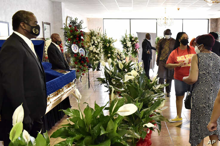 People pay their respects during a memorial service for George Floyd, Saturday, June 6, 2020, in Raeford, N.C. Floyd died after…