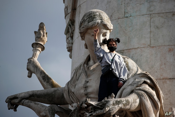 A demonstrator clenches her fist as she stands on a statue on the Place de la Republique during a rally against racism in Paris…