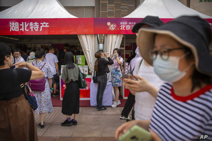 People wearing face masks to protect against the new coronavirus browse merchant tents at a government event aiming to…