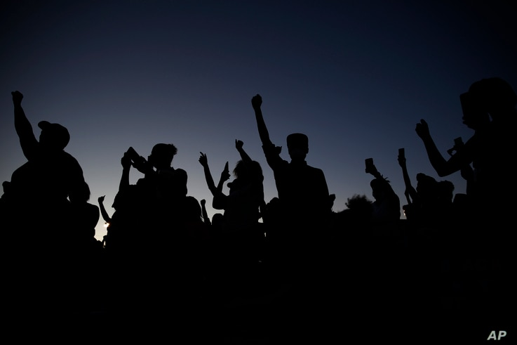 People raise their fists during a rally, Friday, June 5, 2020, in Las Vegas, against police brutality sparked by the death of…
