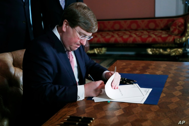 Mississippi Gov. Tate Reeves signs the bill retiring the last state flag in the United States with the Confederate battle...