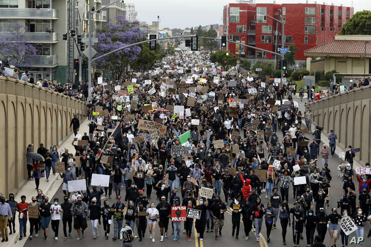 Protestors march Thursday, June 4, 2020, in San Diego. Protests continue to be held in U.S. cities, sparked by the death of…