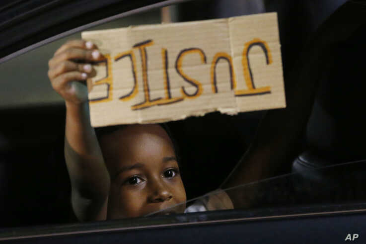 """A young boy holds a """"Justice"""" sign as he peers outside the window of a car passing protesters marching through downtown for a…"""