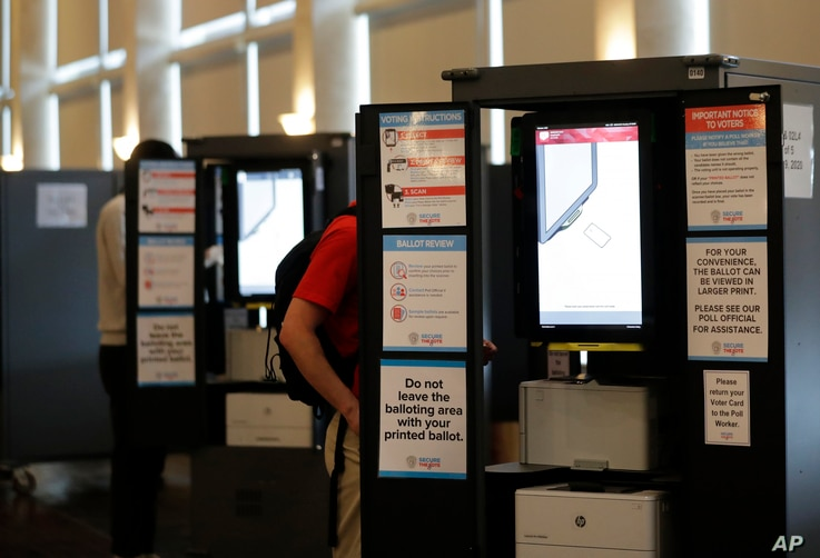 People vote at voting booths in the Georgia's primary election at Park Tavern on Tuesday, June 9, 2020, in Atlanta. (AP Photo…