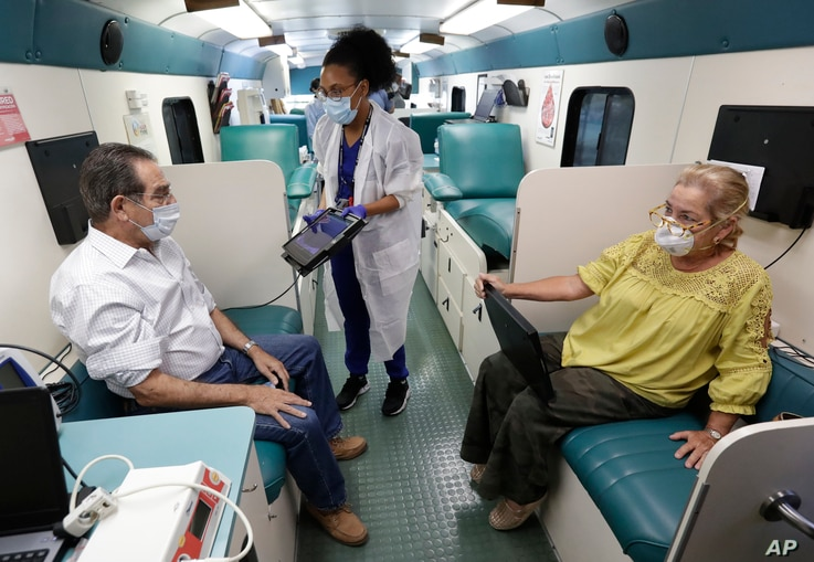 Phlebotomist Sabrina Famiglietti, center, has Miami-Dade County Commissioner Xavier Suarez, left, and wife Rita, right, look…