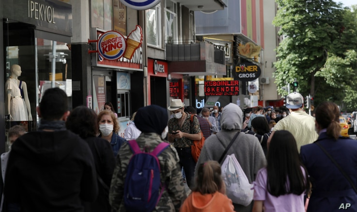 People walk along popular Tunali Hilmi Street, in Ankara, Turkey, Wednesday, June 3, 2020, days after the government lifted a…