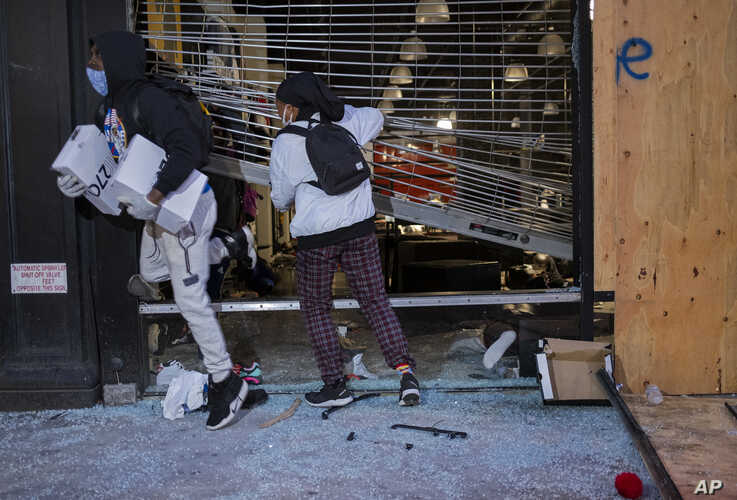People exit damaged stores after the glass was knocked out in the Chelsea neighborhood of New York, Monday, June 1, 2020. (AP…