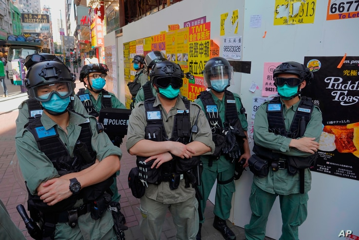 Police officers stand guard as people gather during a pro-democracy rally supporting human rights and to protest against…