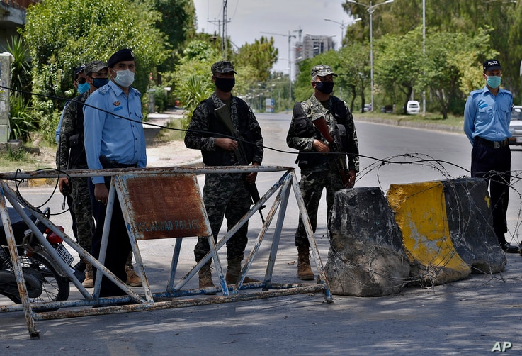 Pakistan paramilitary soldiers and a police officers stand guard at a checkpoint of a restricted area to help to contain the…
