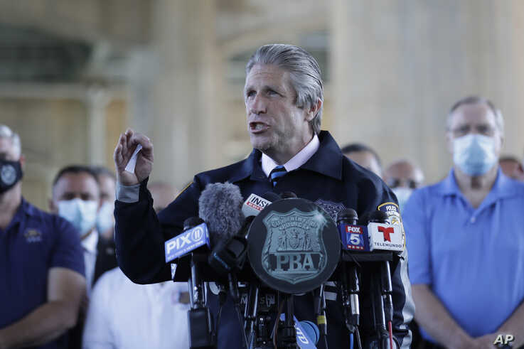 Surrounded by law enforcement and supporters, New York City PBA President Pat Lynch, center, speaks during a news conference in…