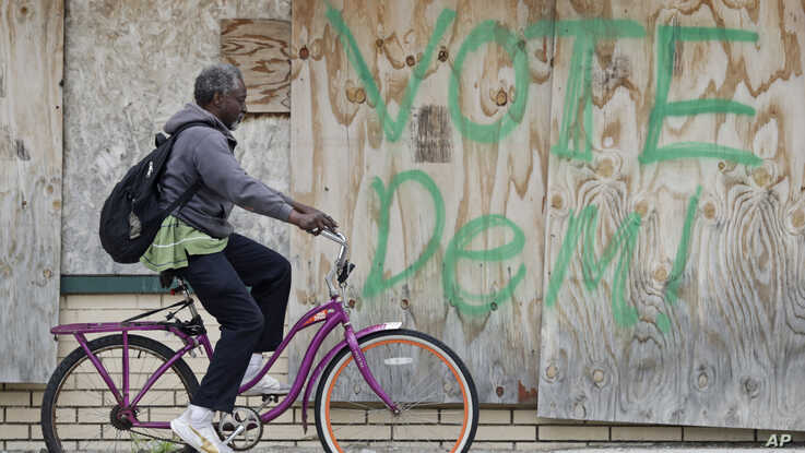 A man rides his bike past a boarded up business, Thursday, May 28, 2020, in East Cleveland, Ohio. The state says about 1.3…
