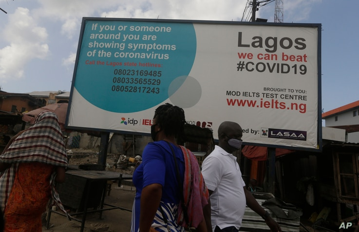 Pedestrian walk past a sign telling resident to call phone numbers if the have coronavirus symptoms in Lagos Nigeria, Tuesday…