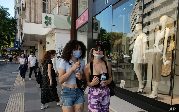People wearing face masks to protect against the spread of coronavirus, walk a in popular shopping street, in Ankara, Turkey,…