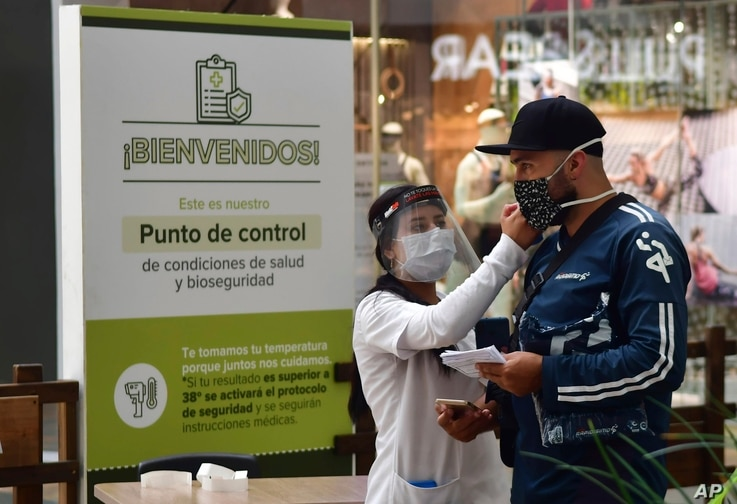 In this June 9, 2020 photo, a nurse measures the body temperature of a shopper at the El Tesoro mall, amid the new coronavirus…