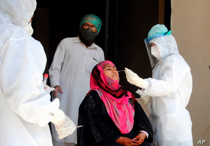 Health workers take a nasal swab sample during a door-to-door testing and screening operation for the new coronavirus, in…