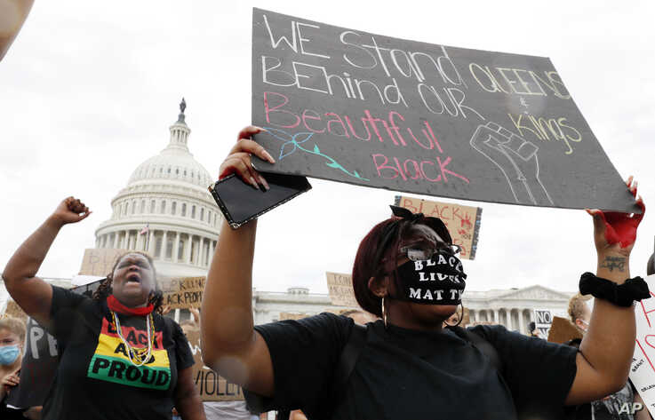 Dominique Bryant, 23, left, and Nastajia Walker, 21, right join demonstrators as they gather to protest the death of George…