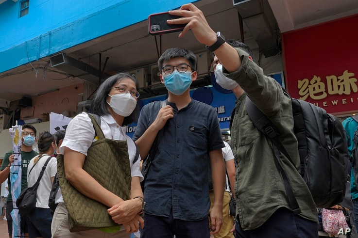 Hong Kong activist Joshua Wong poses for a photo with supporters after attending an activity for the upcoming Legislative…