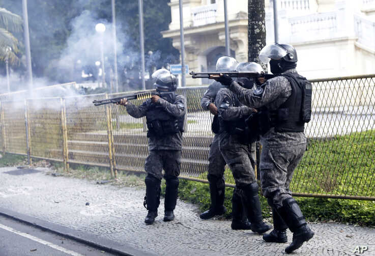 Military police fire the shotguns at demonstrators during a protest against crimes committed by the police against black people…