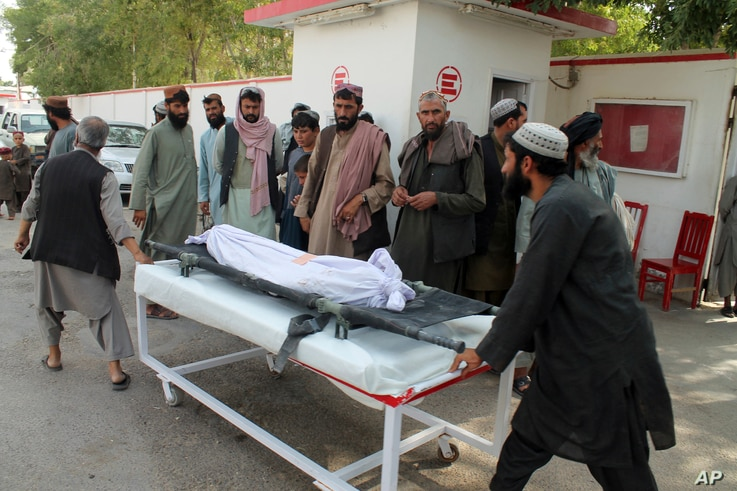 Afghans carry the body of a man who was killed during an attack, in the southern Helmand province, Monday, June 29, 2020. A car…