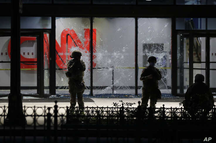 Members of the Georgia National Guard stand in front of shattered glass at the CNN Center in the aftermath of a demonstration…