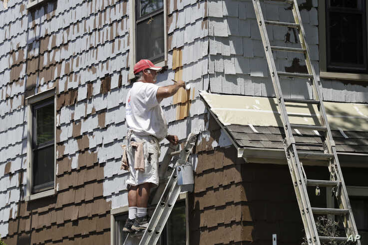 Jm Webb, of Viking Painting, paints the exterior of a house, Friday, June 5, 2020, in Euclid, Ohio. U.S. unemployment dropped…