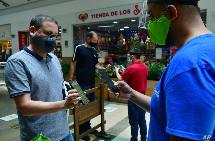 In this June 8, 2020 photo, an El Tesoro mall employee uses his mobile to scan a customer's app to verify he is registered for…