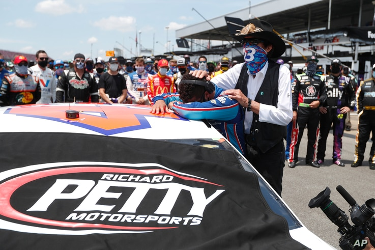 Driver Bubba Wallace, left, is overcome with emotion as team owner Richard Petty, comforts him as he arrives at his car in the…