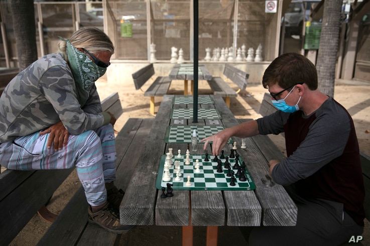 Wearing face coverings, John Williams, right, and Jeff Lee play chess Tuesday, June 23, 2020, in Santa Monica, Calif. The state…