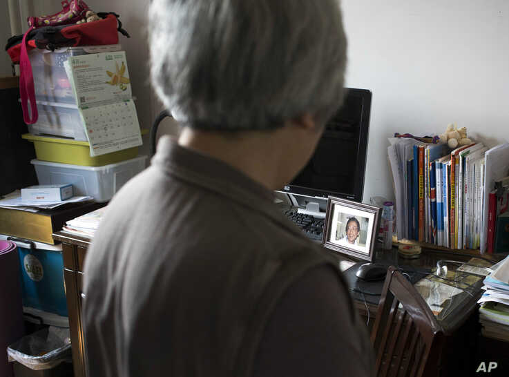 In this photo taken Tuesday, April 29, 2014, Zhang Xianling looks across to a photo of her son Wang Nan who was killed in a…