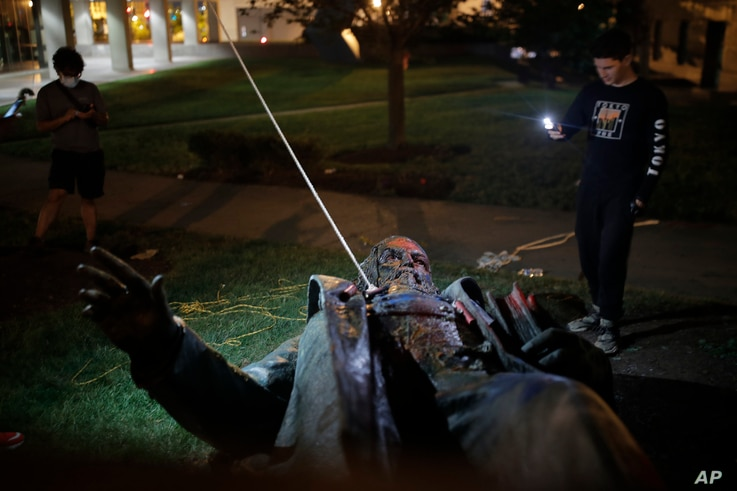 People film the only statue of a Confederate general, Albert Pike, in the nation's capital after it was toppled by protesters…