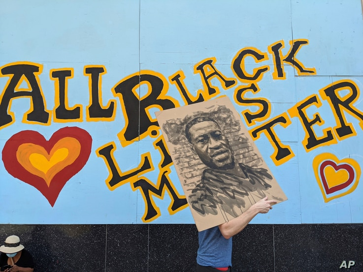 "A demonstrator carries an image of George Floyd in front of a boarded up business decorated with a mural reading ""All Black…"