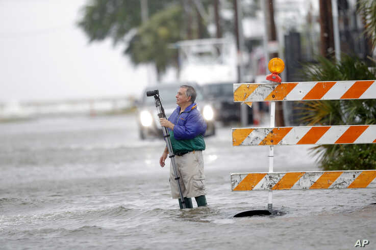 Charles Marsala, who lives in the Orleans Marina in the West End section of New Orleans, films a rising storm surge from Lake…