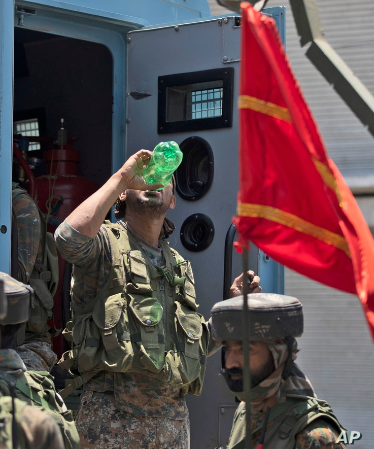 An Indian soldier drinks water as they return from the site of a gun-battle in Srinagar, Indian controlled Kashmir, Sunday,…