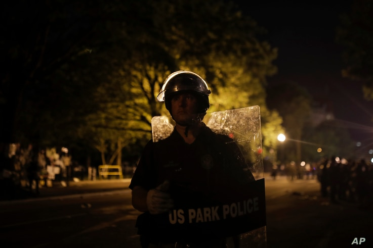 A. U.S. Park Police officer stands as police close the area around Lafayette Park near the White House after protesters tried…