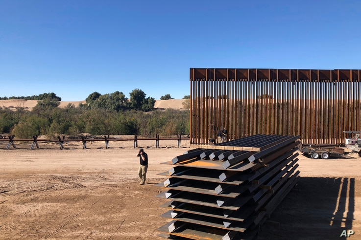 In this Jan. 10, 2020, photo, people work at a portion of border wall which is under construction in Yuma, Ariz. Illegal border…