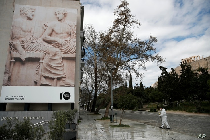 A municipal worker wearing a protective suit sprays disinfectant outside Acropolis museum as the Parthenon temple is seen in…
