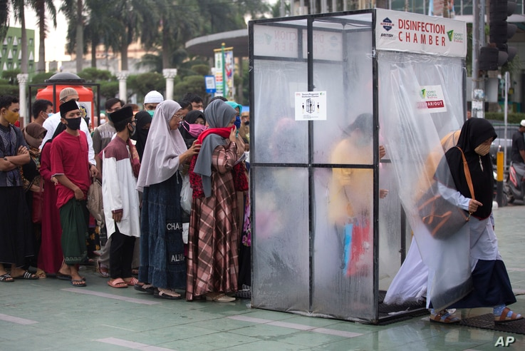 Muslims queue up to enter a disinfection chamber set up as a precaution against the new coronavirus outbreak, upon arrival for…