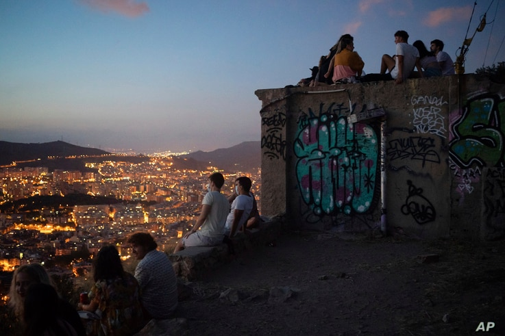 People gather outdoors at dusk on a viewpoint in Barcelona, Spain, Saturday, July 25, 2020. Britain is advising people not to…