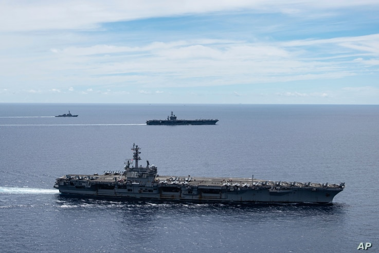 In this photo provided by U.S. Navy, the USS Ronald Reagan (CVN 76, front) and USS Nimitz (CVN 68, rear) Carrier Strike Groups…