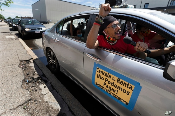 FILE -  In this May 30, 2020, file photo, a car caravan calling for the cancellation of rents during the coronavirus pandemic…