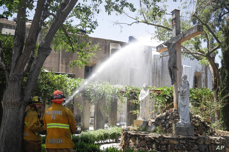 Firefighters hosed down hot spots in the aftermath of a morning fire at the San Gabriel Mission Saturday, July 11, 2020, in San…