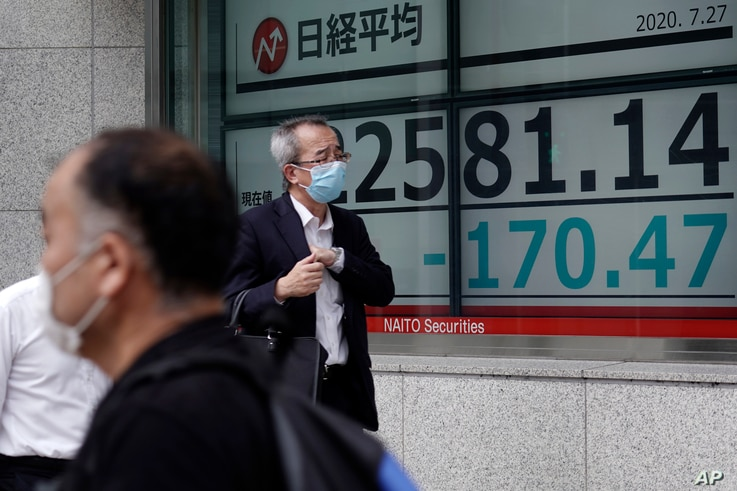 Men walk past an electronic stock board showing Japan's Nikkei 225 index at a securities firm in Tokyo Monday, July 27, 2020…